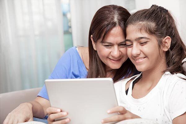 Mother and daughter watch online video with Turkish subtitles on a tablet.