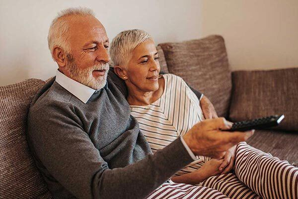 Elderly couple watch TV with closed captions on.