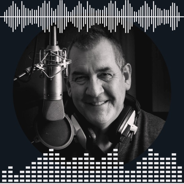 Senior male narrator with headphones sits smiling in front of studio mic.