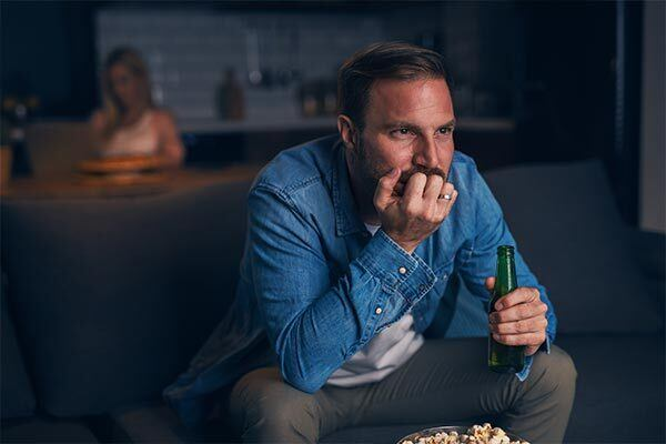 German man eagerly watches TV with German subtitles whilst drinking beer.
