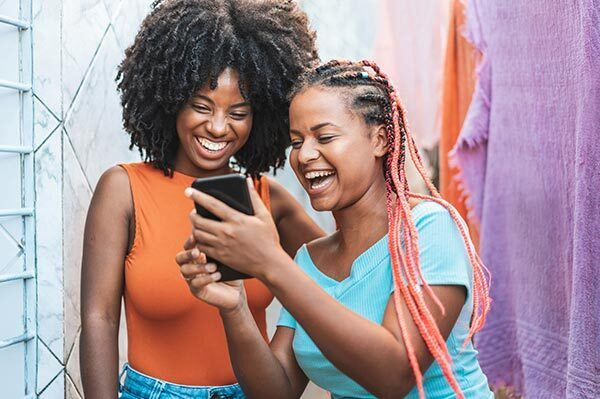 Two black woman laughing at a comedic animation on their phone.