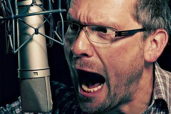 Male German voice-over talent shouts into microphone.
