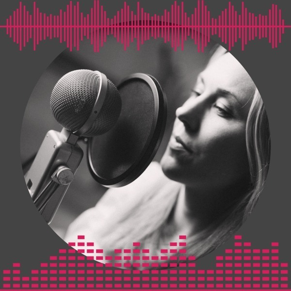 Blonde female voice-over talent reads into mic.