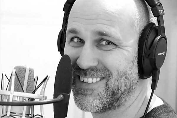Swedish male voice-over talent with headphones, smiles behind microphone.