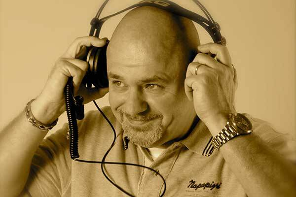 Bald Italian male voice-over talent puts headphones on and smiles.
