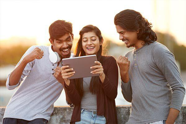 Friends watch TV on a tablet with Hindi subtitles.