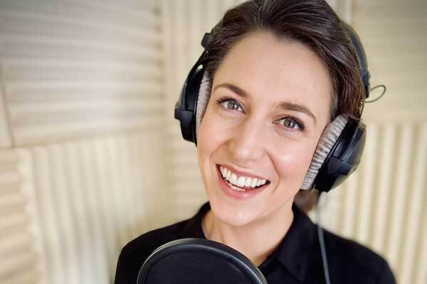 Scottish female voice-over talent smiling in home studio booth.