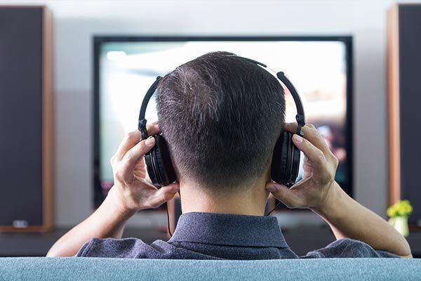 Blind person listening to audio description watching TV series.