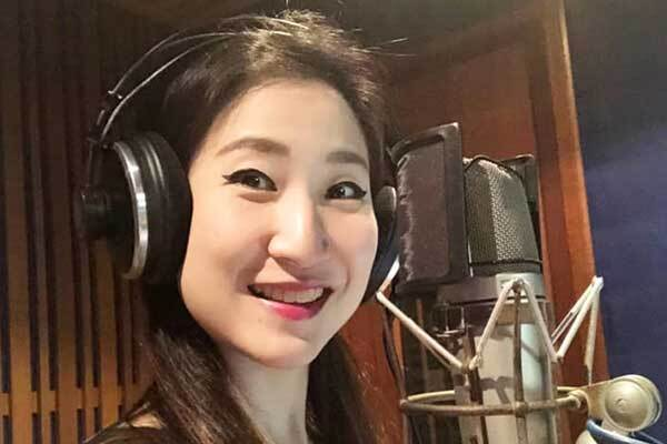 Thai female voice-over talent in studio, turns to camera smiling.