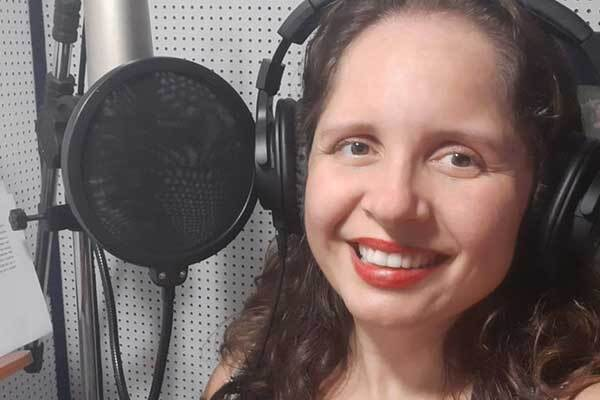Brazilian Female voice-over talent, smiling at camera with mic in background.