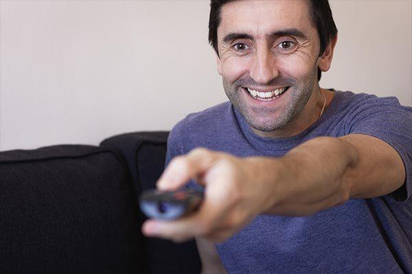 Smiling Israeli man watches TV series with Hebrew subtitles.