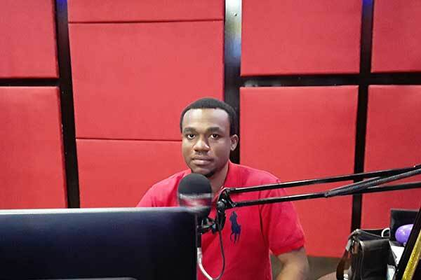 Male Nigerian voice-over talent in studio with red acoustic tiles.