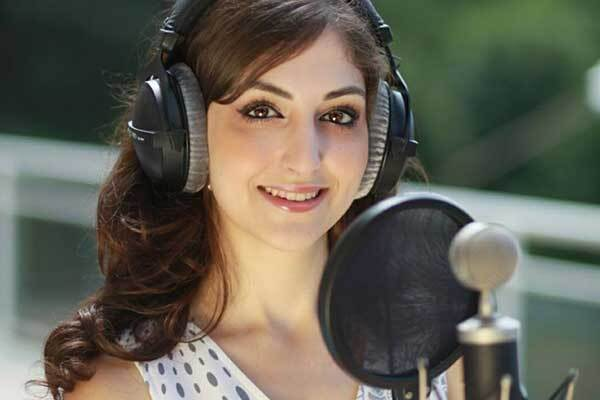 French female voice-over talent smiles, wearing headphones in front of studio mic.