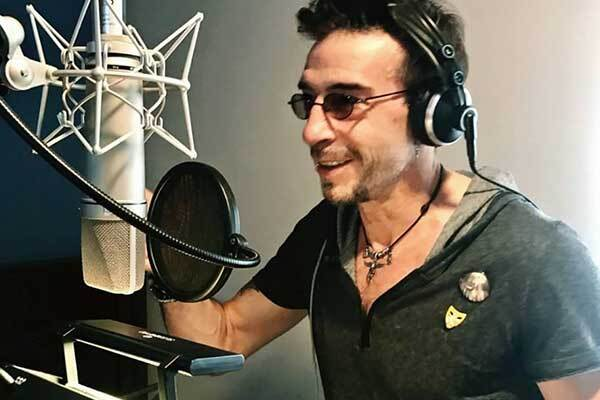 Spanish voice-over talent, smiles with glasses on, sitting behind mic.