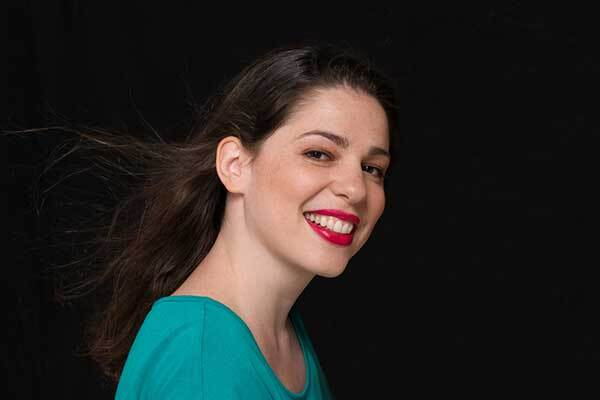 Dark-haired Greek female voice-over talent with red lipstick smiles at camera.