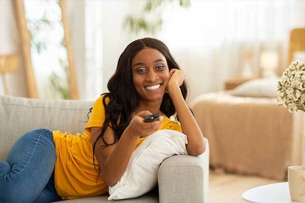 Black American woman watches movie with English subtitles.