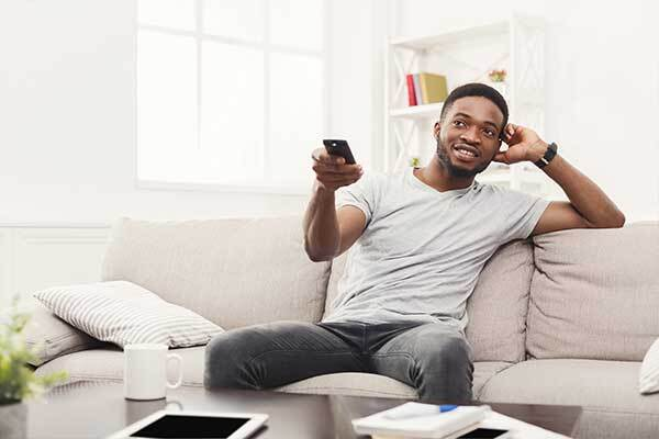 Black Norwegian man watches Netflix show with Norwegian subtitles.