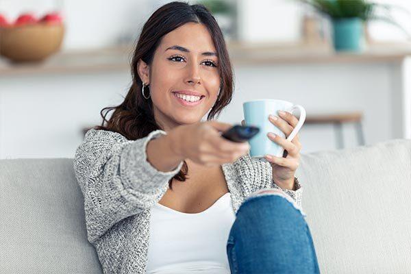 Pretty Spanish woman, holding coffee mug, watches TV with Spanish subtitles.
