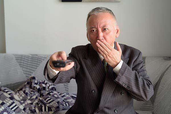 Japanese businessman watches TV series with Japanese subtitles.