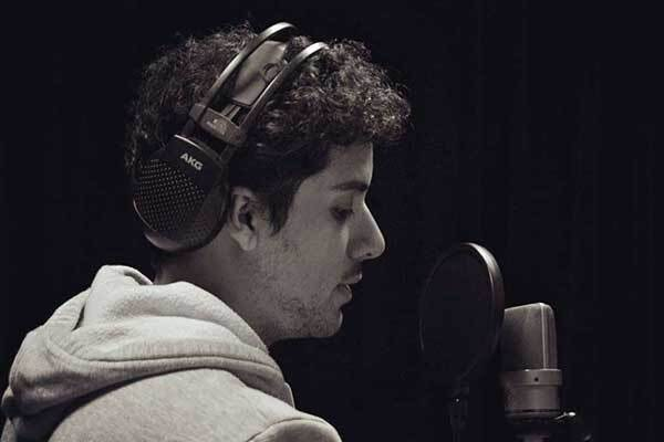 Male Argentinean voice talent in dark room with headphones on.